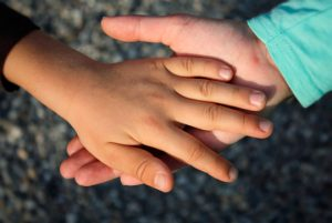 Adult holding child's hand to illustrate Child Protection